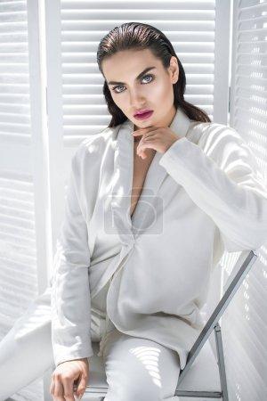 femme belle glamour, posant en costume à la mode blanc