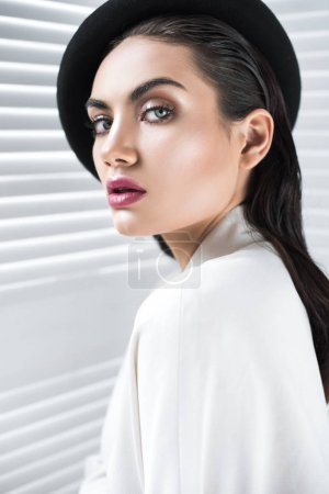 fashionable woman with glamour makeup posing in beret and elegant white jacket