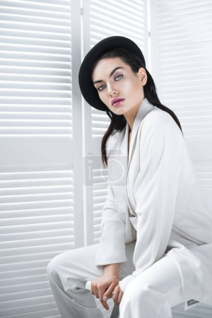 attractive woman posing in beret and white fashionable jacket