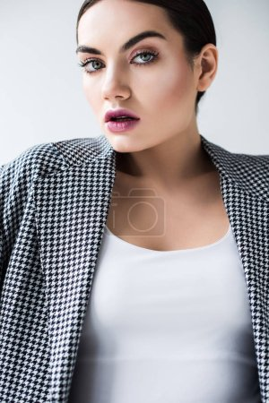 attractive stylish woman with makeup posing in vintage jacket, isolated on grey