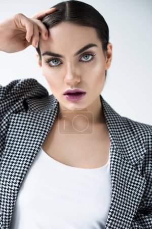 attractive girl with makeup posing in vintage jacket, isolated on grey