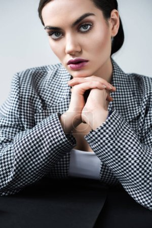 fashionable woman with makeup posing in elegant retro suit, on grey
