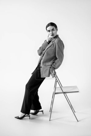 beautiful glamour model posing in fashionable vintage suit near chair, on grey, black and white