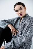 beautiful fashionable girl with makeup posing in vintage elegant jacket, isolated on grey