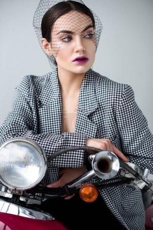 elegant woman in jacket and net veil posing on retro classic scooter, isolated on grey