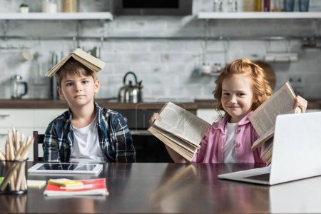 adorable little kids with lot of books looking at camera at kitchen