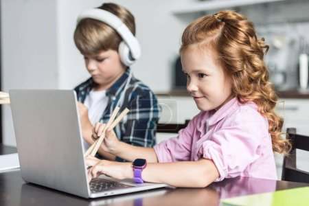 Photo for Little brother and sister doing homework and using laptop - Royalty Free Image