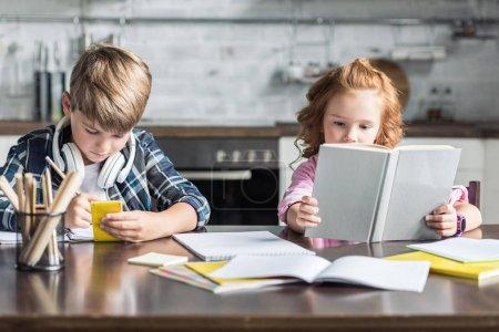 Photo pour Concentré de petits frères et sœurs à faire leurs devoirs ensemble à la cuisine - image libre de droit