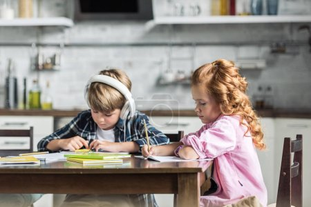 Photo for Focused little kids doing homework together at kitchen - Royalty Free Image