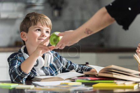 cropped shot of mother giving green apple to her son while he doing homework