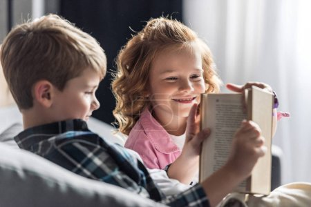 little boy reading book while his sister interrupting him