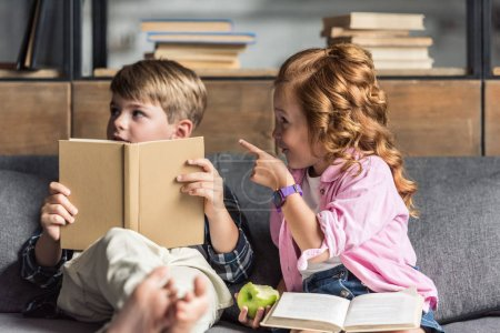 cute little schoolboy reading book on couch while his sister pointing somewhere