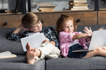 little brother and sister using digital devices while relaxing on couch