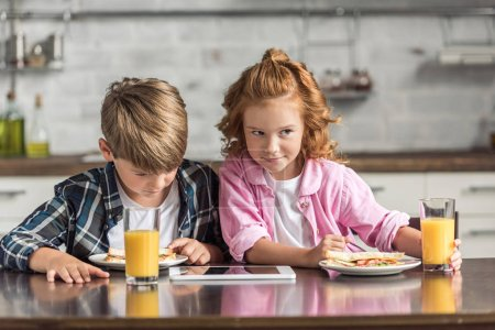 Photo for Cute little brother and sister using tablet during breakfast at kitchen - Royalty Free Image