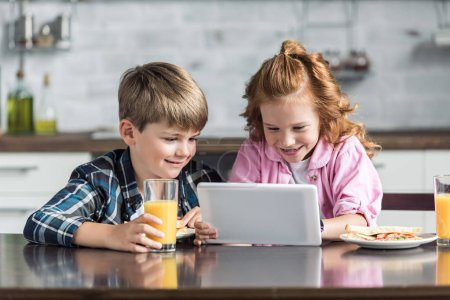 smiling little brother and sister using tablet during breakfast