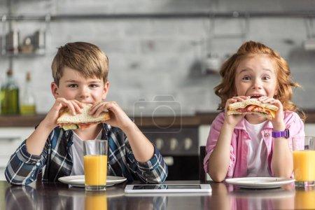 entzückende kleine Bruder und Schwester essen Sandwiches und schauen in die Kamera