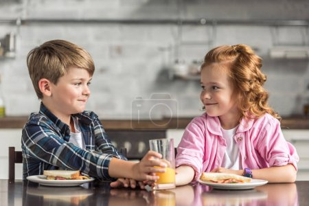 little brother and sister reaching for glass of orange juice during breakfast and looking at each other