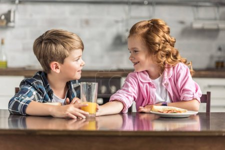 happy little brother and sister eating breakfast and looking at each other