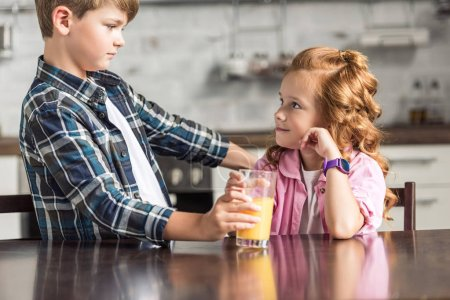 little brother giving glass of orange juice to his sister