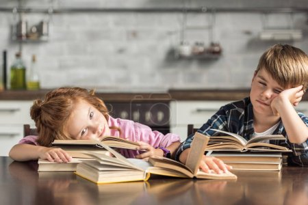 tired little scholars sleeping on book while doing homework