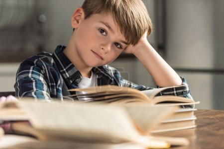 bored little schoolboy with books on table looking at camera