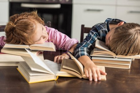 exhausted little scholars sleeping on book while doing homework