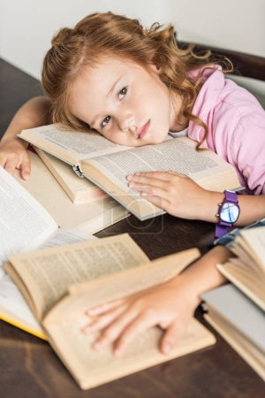 high angle view of exhausted little schoolgirl lying on books