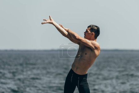 athletic shirtless man dancing in front of sea view