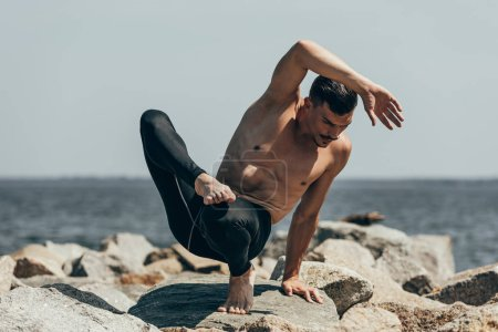 handsome shirtless man performing contemporary dance on rocky coast