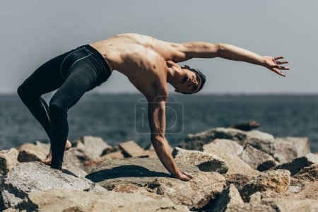 handsome shirtless contemporary dancer on rocky coast
