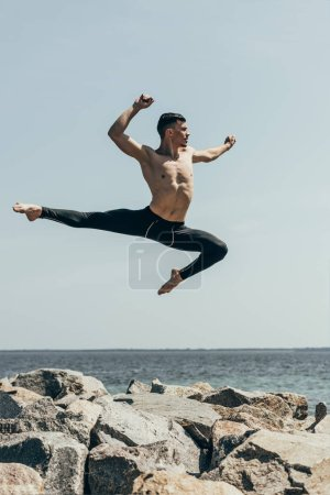athletic shirtless dancer jumping over rocky seashore