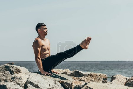 Photo for Athletic shirtless man doing arm balance on rocky seashore - Royalty Free Image