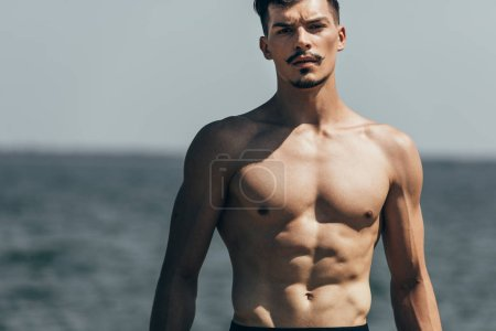 handsome athletic man looking at camera in front of sea