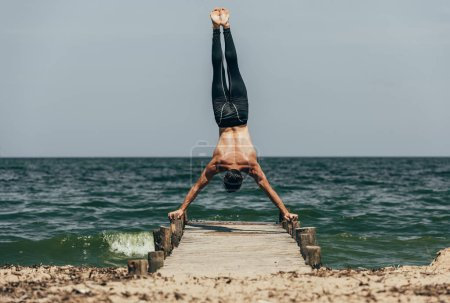 handsome shirtless man performing handstand on wooden pier