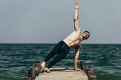 sporty shirtless man doing side plank on wooden pier
