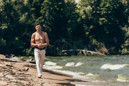 attractive shirtless man walking by sandy beach