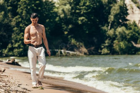 handsome shirtless man looking at his hand and walking by sandy beach
