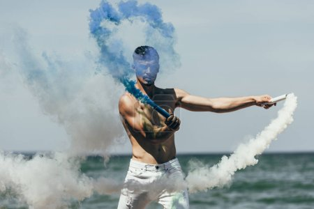 attractive man holding blue and white smoke sticks in front of sea