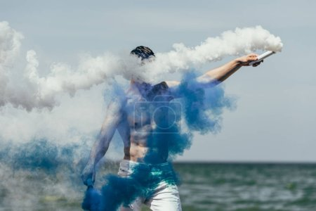 shirtless man with blue and white smoke sticks in front of ocean