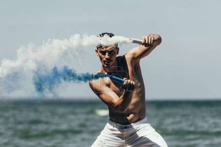 muscular shirtless man dancing with blue and white smoke sticks in front of ocean