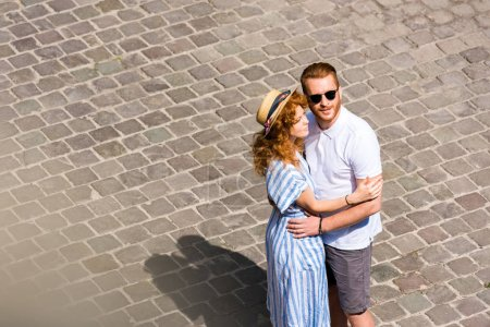 Photo for Redhead man in sunglasses embracing girlfriend at city street - Royalty Free Image