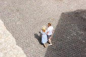 high angle view of redhead couple holding hands and walking at city street