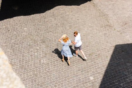 Photo for High angle view of redhead woman in straw hat walking and holding hand of boyfriend at city street - Royalty Free Image