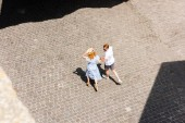 high angle view of redhead woman in straw hat walking and holding hand of boyfriend at city street