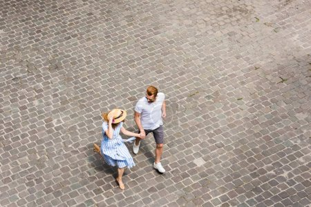 Photo for High angle view of woman in straw hat walking with redhead boyfriend at city street - Royalty Free Image