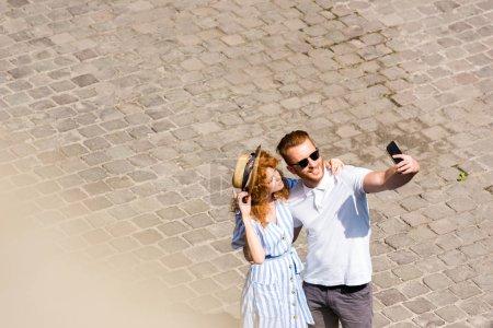 Photo pour Vue grand angle homme rousse en emportant selfie amie sur smartphone à rue de la ville de soleil souriant - image libre de droit