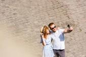 """Постер, картина, фотообои """"высокий угол зрения улыбается человек рыжая в солнцезащитные очки с подругой на смартфоне на улице города selfie"""""""