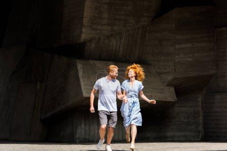 Photo pour Smiling couple rousse, main dans la main à la rue de la ville - image libre de droit