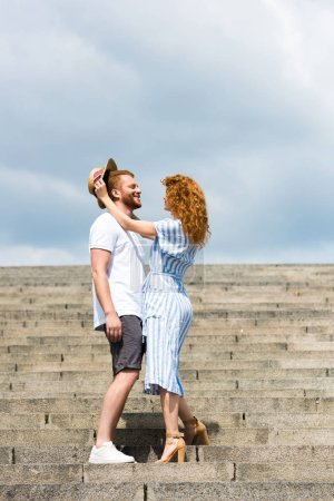Photo for Attractive redhead woman putting on own straw hat on boyfriends head on stairs - Royalty Free Image