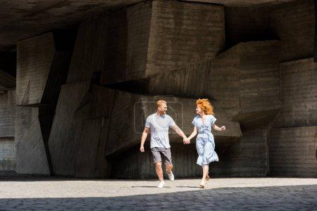 Photo pour Couple heureux rousse, main dans la main à la rue de la ville - image libre de droit